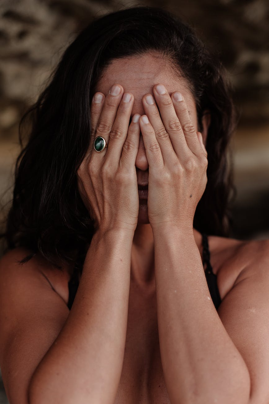 photo of woman covering her face